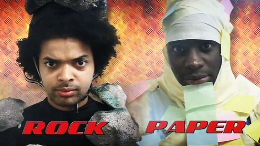 Johnny and Inel dressed as Rock and Paper, looking angry.