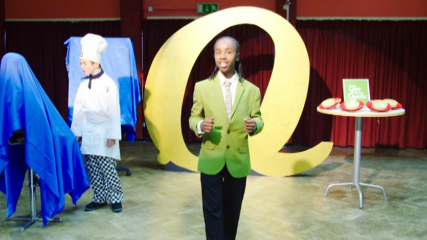 Nero wearing a green suit standing in front of a giant letter Q.