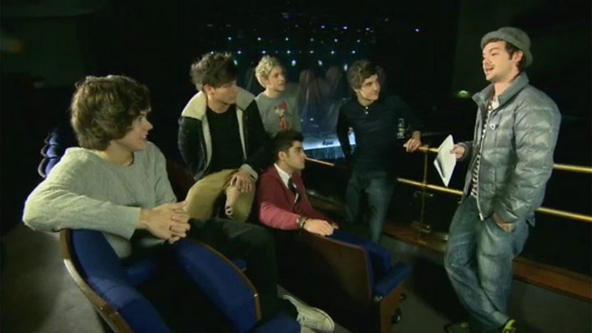 One Direction sat in the audience seats of a theatre.