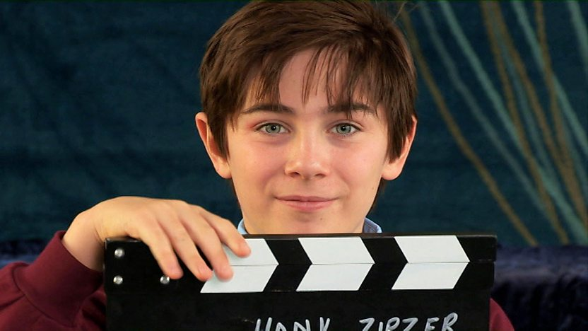 Nick James, who plays Hank Zipzer, holding a clapperboard.