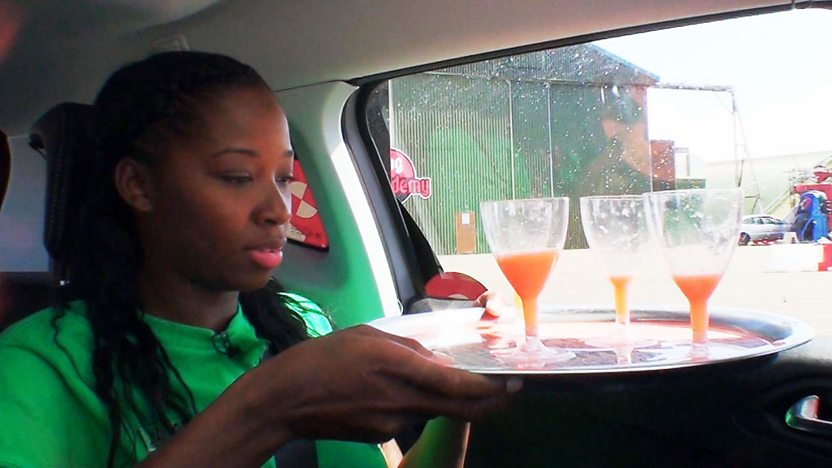 Jamelia in the back of a car, trying to hold a tray of drinks steady.