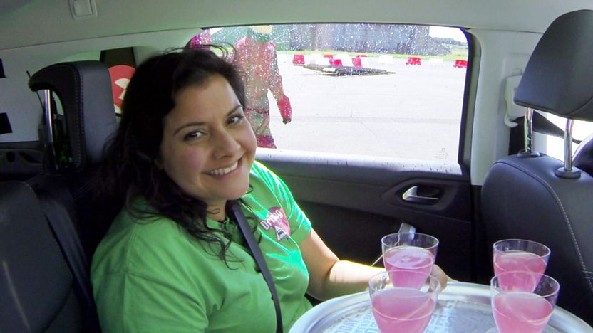 Nina Wadia in the back of a car, trying to hold a tray of drinks steady.
