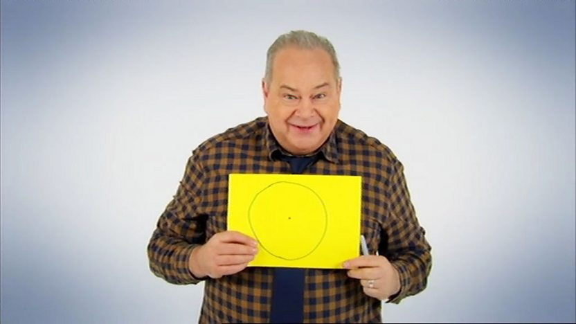 John from Help My School Trip is Magic, holding a piece of paper with a circle and a dot on it.