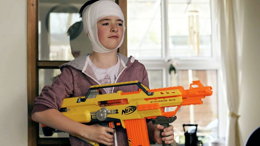 Louis holding a toy gun with his head wrapped up in bandages.