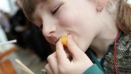 Niña comiendo mandarina