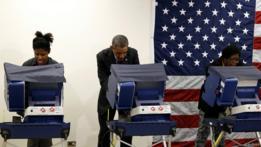 Obama votando entre dos mujeres