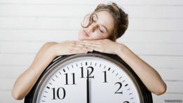 Chica durmiendo en un reloj