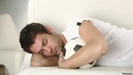 Una persona dormida con una pelota de fútbol