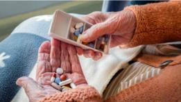 Una persona anciana con medicinas en la mano