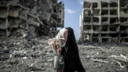 Mujer palestina carga a menor frente a escombros