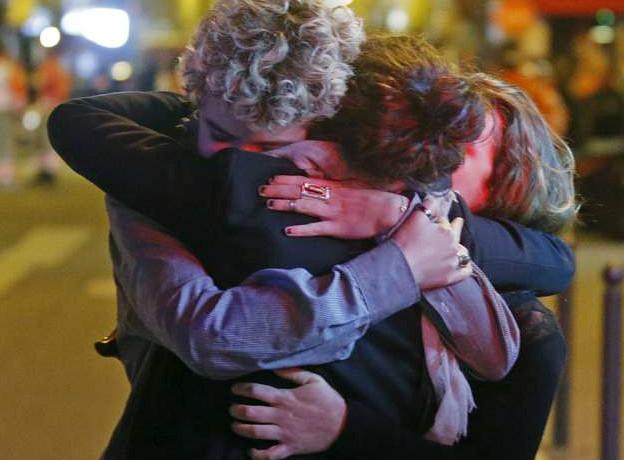 Люди обнимают друг друга рядом с театром Батаклан