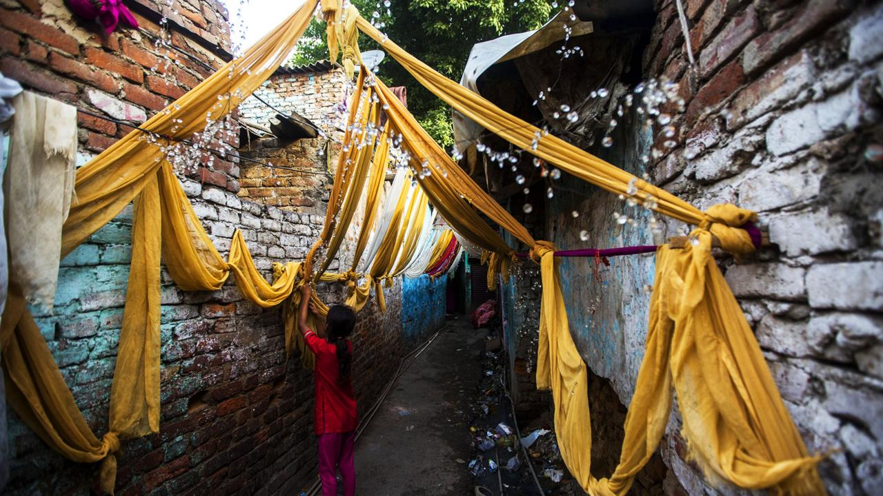 A young girl decorates a Kathputli alleyway (Credit: Credit: AFP/Getty)