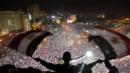 A man waves Egyptian flags above Tahrir Square (Credit: Photo: AP)