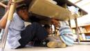 School children take cover under desks during an earthquake drill. (Getty) (Credit: Getty)