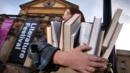 A woman carries a stack of books (Credit: Alamy)
