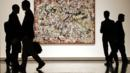 Viewers in a gallery stand in front of a painting by Jackson Pollock (Credit: Corbis)