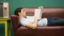A young man reads a book on a sofa (Credit: Corbis)