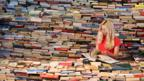 Woman looks at a book in the aMAZEme labyrinth, London (Copyright:Getty Images)