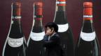 A man on a phone walks past an advertisement for wine