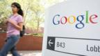 A woman walks past a sign at one of Google's buildings