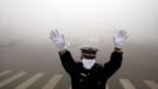 Directing traffic in smoggy downtown Beijing (AFP)
