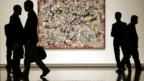 Viewers in a gallery stand in front of a painting by Jackson Pollock