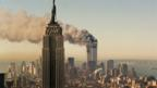 The twin towers of the World Trade Center burn behind the Empire State Building