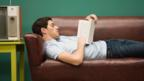 A young man reads a book on a sofa