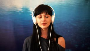 A woman listens to music on headphones