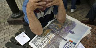Man reads newspaper (AFP/Getty Images)