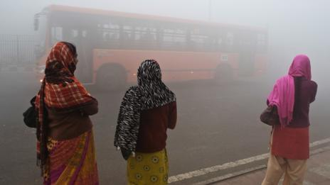 Women wait for a bus in Dehi, under polluted skies. (Prakash Singh/AFP/Getty Images)