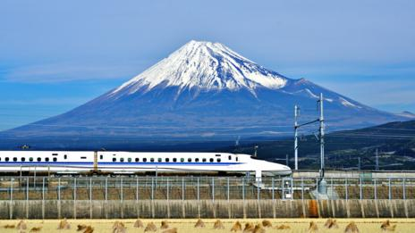 A bullet train speeds past a majestic Mount Fuji in Japan (Sean Pavone/Alamy)