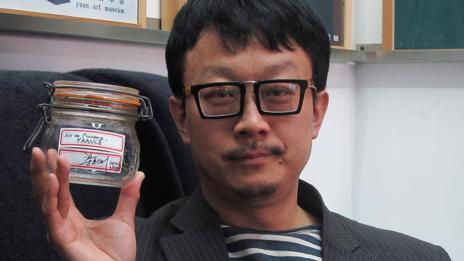 Beijing artist Liang Kegang with a jar of fresh air from France (AP Photo/Didi Tang)