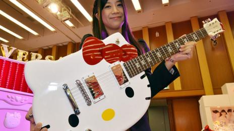 A Sanrio employee holds a Hello Kitty guitar (Yoshikazu Tsuno/AFP/Getty Images)