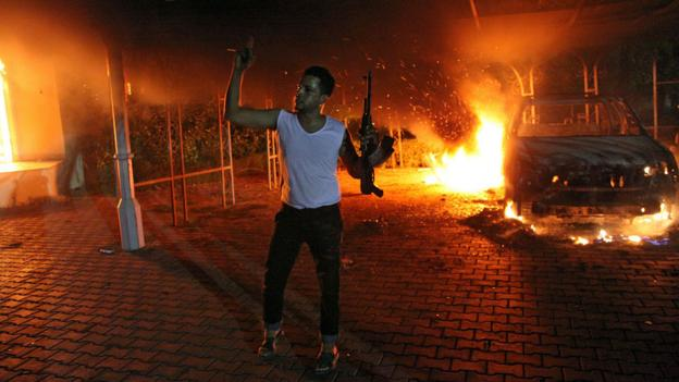 A man waves a rifle outside the US conculate in Benghazi (Copyright: Getty Images)