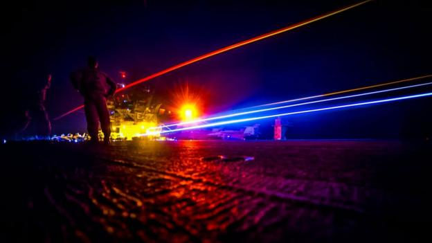 Lights shine across the deck of a warship (Copyright: US Navy)