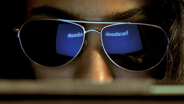 Girl looks at Faccebook page wearing sunglasses (Copyright: Getty Images)