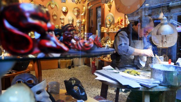 A craftman makes Venetian masks in his workshop (Credit: Vincenzo Pinto/AFP/Getty)