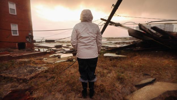 A woman surveys damage in the aftermath of Hurricane Sandy.