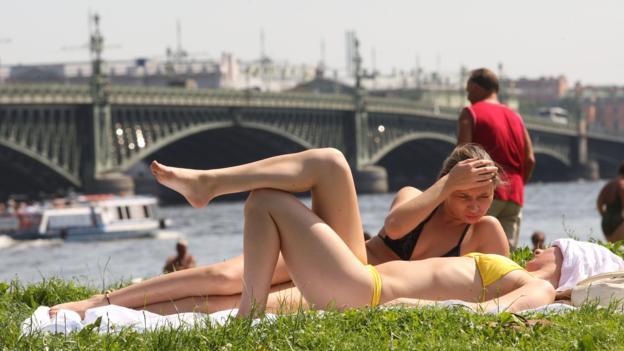 Sunbathing on the banks of the Neva River (Credit: Kirill Kudryavtsev/AFP/Getty)