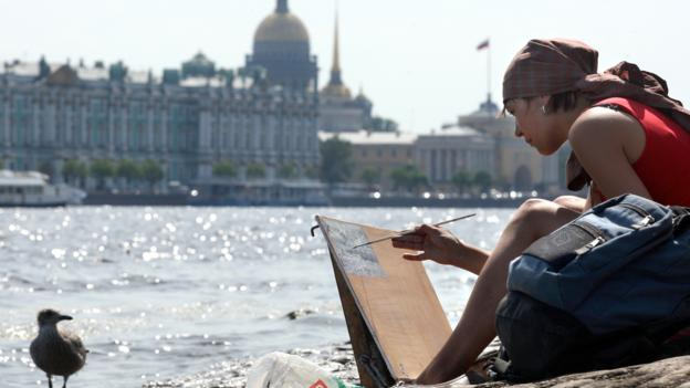 Painting on the banks of the Neva River (Credit: Kirill Kudryavtsev/AFP/Getty)