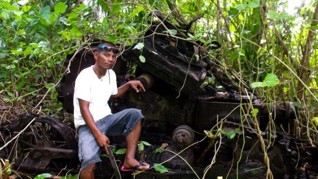Sylvester Clement poses by a Japanese tank (Credit: Sameena Jarosz)