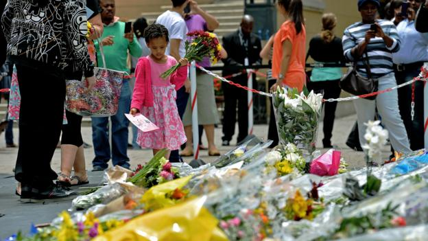 A young girl lays flowers in memory of Nelson Mandela in Sandton (Credit: Carl de Souza/AFP/Getty)