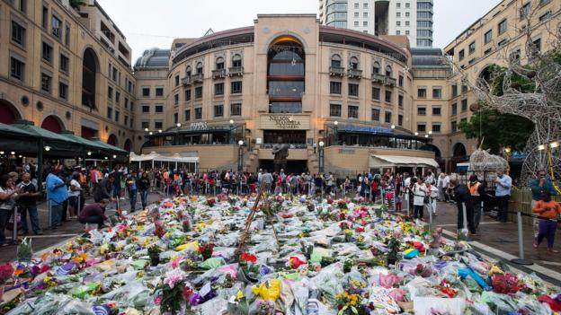 People lay flowers in Nelson Mandela Square, Johannesburg (Credit: Brent Stirton/Getty)
