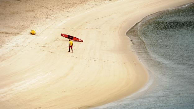 A lifeguard walks along the Palawan Beach lagoon (Credit: Roslan Rahman/AFP/Getty)