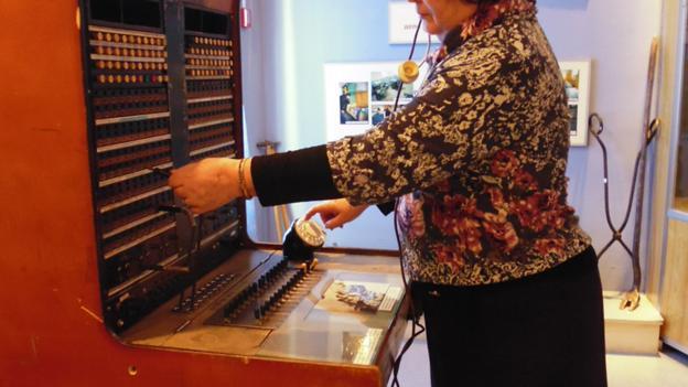 A Tynda museum attendant demonstrates a 1980s phone (Credit: Anna Kaminski)