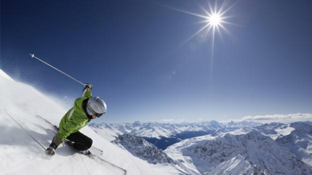 A skier descends from the top of a peak overlooking Davos, Switzerland (Thinkstock)