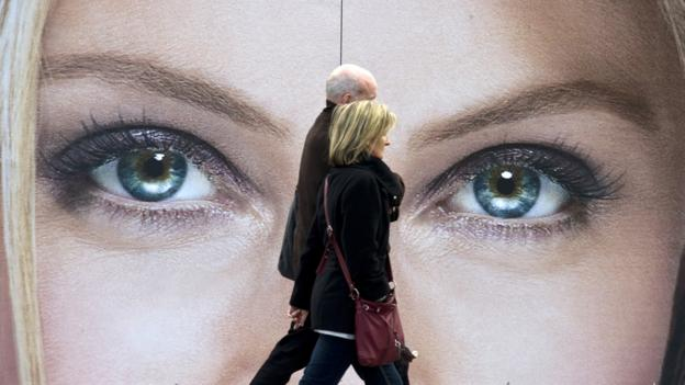 People walking in front of eyes on billboard (AFP/Getty)