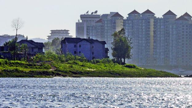 Dandong's buildings dwarf the North Korean coastline (Credit: Natalie Behring-Chisholm/Getty)