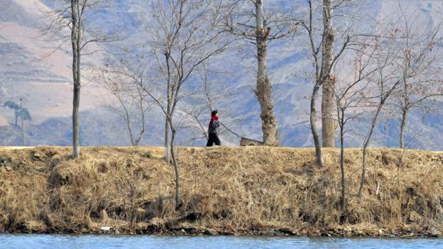 A North Korean woman on the banks of the Yalu River (Credit: Frederic J Brown/AFP/Getty)